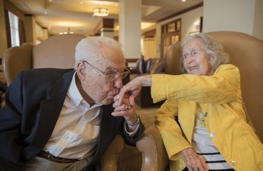John Henderson kisses his wife, Charlotte, on the hand Nov. 12 at Longhorn Village retirement community. The Hendersons are the oldest living married couple on the planet, according to Guinness World Records.