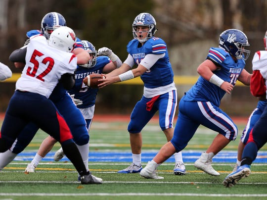 Westfield quarterback Hank Shapiro hands off the ball against Plainfield during their annual Thanksgiving Day game on Thursday, Nov. 28, 2019.