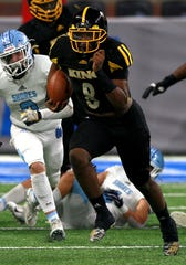 The Muskegon Mona Shores defense tries to catch Detroit Martin Luther King #8 Peny Boone from running for extra yardage during the first half of the Division 2 football game between Muskegon Mona Shores and Detroit Martin Luther King at Ford Field on Friday, November 29, 2019.Muskegon Mona Shores won the game and the Division 2 state championship 35-26