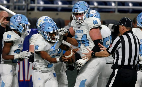 Muskegon Mona Shores' Khyree Hamel hands the football to a referee and starts to celebrate a touchdown with teammates in the first half of Mona Shores' 35-26 win in the Division 2 state final at Ford Field on Friday, Nov. 29, 2019.