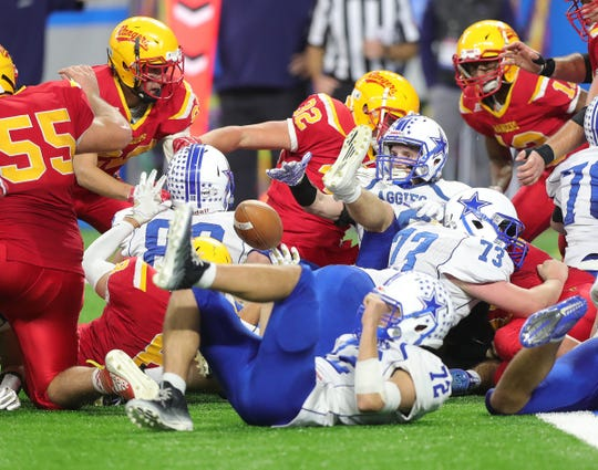Reading defenders cause a fumble by Beal City's Ben Matthews (30) during Reading's 33-6 win in the Division 8 state championship game on Friday, Nov. 29, 2019, at Ford Field.