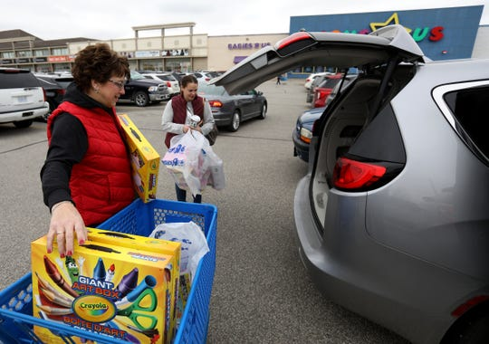 (L to R) Ann Bedra, 62 of Southgate and her daughter-in-law Chevelle Bedra, 34 of Flat Rock load up the minivan with items they bought at the Toys R Us in Windsor, Ontario, Canada on Friday, November 29, 2019. With all Toys R Us stores closed in Michigan, the Bedras are two of many people from Michigan that cross the boarder to shop at the only Toys R Us nearby.