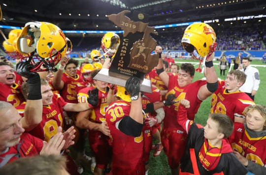 Reading's Elijah Strine (30) raises the championship trophy after Reading's 33-6 win in the Division 8 state championship game on Friday, Nov. 29, 2019, at Ford Field.