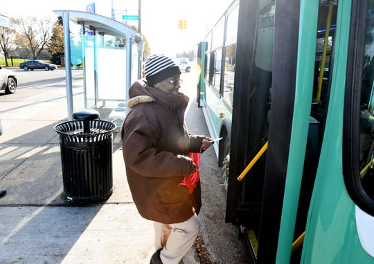 Kathleen Roland, 71, of Detroit, boards a  bus from one of the new DDOT bus stop shelters at the corner of Livernois and West McNichols in Detroit.