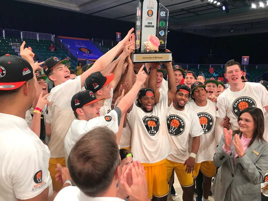 The Michigan basketball team celebrates with its Battle 4 Atlantis trophy.