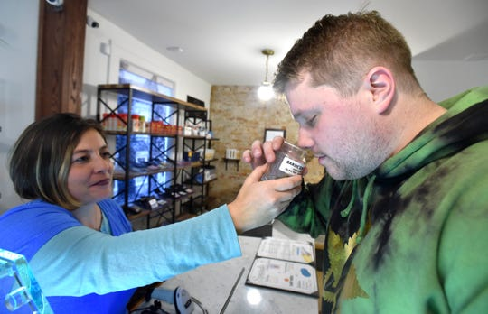 Patient Ryan Sculthorpe, of Canton, smells a bud of Garlic Cookies, an Indica strain, as consultant Evie holds the display jar at Arbors Wellness in An Arbor. Recreational marijuana is expected to begin sales on Sunday, December 1. Arbors Wellness is a medical marijuana dispensary with a recreational license.