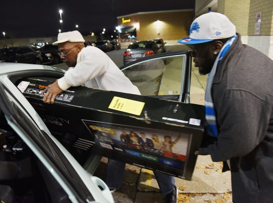 Alvin Cook of Inkster and Chris Jones of Detroit try to squeeze a 55-inch television into a Ford Fiesta outside of Best Buy.