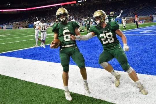 Monroe St. Mary Catholic Central quarterback Wyatt Bergmoser, left, runs through the end zone for a touchdown in the Division 6 state championship game.