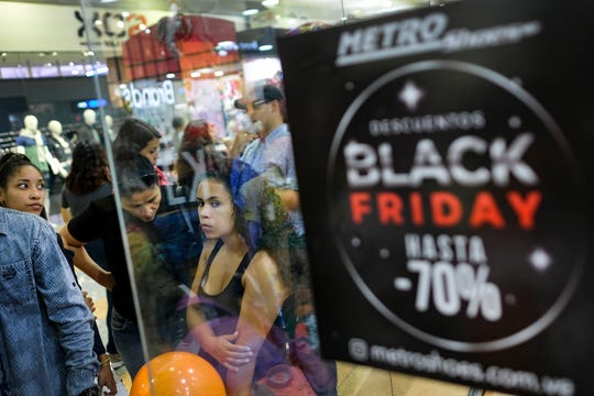 Shoppers stand near a sign promoting Black Friday sales at the Sambil shopping center in Caracas, Venezuela, Friday, Nov. 29, 2019.