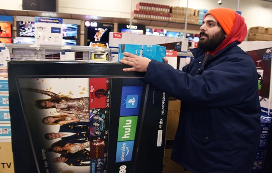 Ali Kondil, 27, of Dearborn Heights carries a 58 inch Insignia television that he intends to purchase.