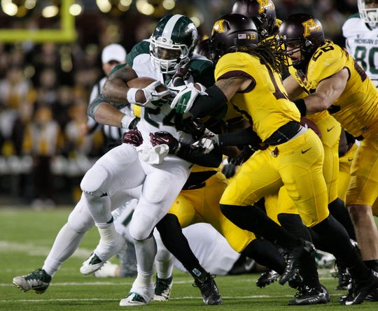Le'Veon Bell carries Minnesota defenders during Michigan State's 26-10 win in 2012.