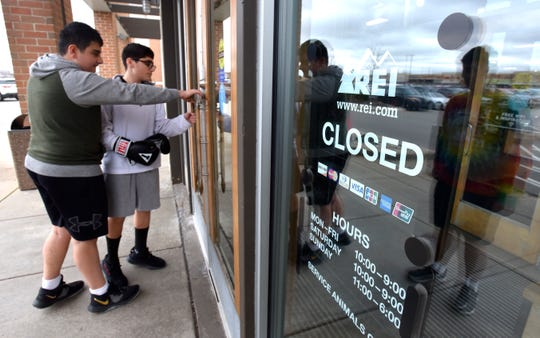 Alex Altaweel, left, 15, of Troy, and his cousin pull on the locked door at REI (Recreational Equipment Inc.) in Troy on Black Friday. Since 2015, REI has closed its doors on Black Friday as part of the #OptOutside movement. The company pays its13,000-plus employees to reconnect outdoors with family members and friends over the holidays.