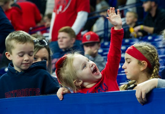 Helen Heeke, 3, center, of Evanston, Ind., welcomes the Patriots to the field at the Heritage Hills vs Bishop Chatard IHSAA State Football Game at Lucas Oil Stadium in Indianapolis, Ind., Friday, Nov. 29, 2019. Bishop Chatard won 34-3 over No. 2 Heritage Hills.