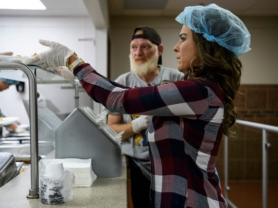 "Holly Byers gets a plate from the kitchen as she and Harold Jones, back, prepare to serve meals to men attending the free lunch at Evansville Rescue Mission, Monday afternoon, Nov. 25, 2019. ""I love to help others. I don't like to call it volunteering because I feel like that's a selfish word."" Byers said. ""I call it opportunity, actually, because they're doing something for you, too."