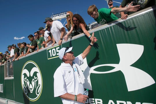 CSU coach Mike Bobo slaps the hands of Rams fans after a 58-27 win over Oregon State in the teams season opener, the first regular-season game held at the new on-campus stadium on Saturday, August 26, 2017.