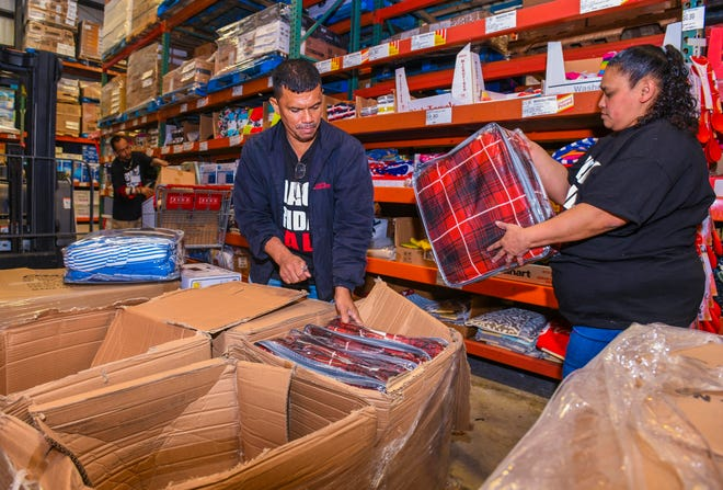 Employees get merchandise out on the floor at the Cost-U-Less in Tamuning in this Nov. 29, 2019, file photo.