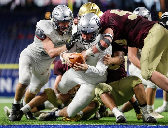 Lafayette Central Catholic quarterback Clark Barrett (4) pushes into the end zone at the IHSAA Class A state finals at Lucas Oil Stadium, Friday November 29, 2019. Lafayette Central Catholic defeated Lutheran for the championship, 29-28.