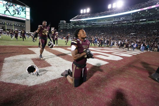 Mississippi State's Kylin Hill (8) kneels in the end zone following the win. MSU players celebrate after winning the Egg Bowl 21-20. Mississippi State and Ole Miss played in the Egg Bowl on Thursday, November 28, 2019 at Davis Wade Stadium in Starkville.