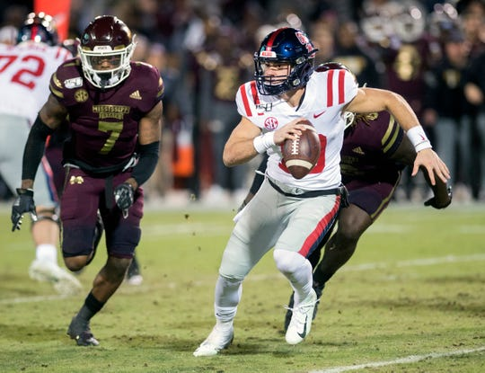 With Bulldogs #7 Marcus Murphy, left, and #6 Willie Gay Jr., right,  on his heals, Ole Miss quarterback John Rhys Plumlee makes his way down the field on a keeper during the Egg Bowl at Davis Wade Stadium in Starkville Thursday, Nov. 28, 2019.