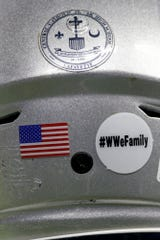 "A ""#WWeFamily"" sticker on the back of a Central Catholic helmet in honor of the late West Washington's head coach Phillip Bowsman, who died Monday, Friday, Nov. 29, 2019 at Lucas Oil Stadium in Indianapolis."