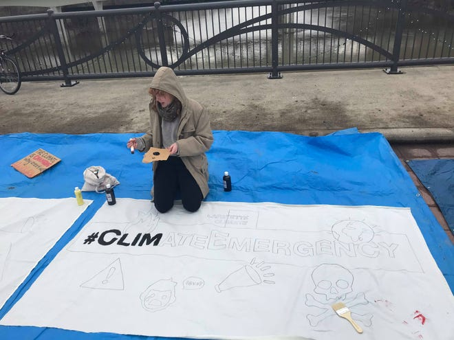 """Polly Barks, a co-facilitator with the group Lafayette Climate, works on painting a banner that reads """"#ClimateEmergency"""" during the Bridge Across the Climate Crisis strike."""