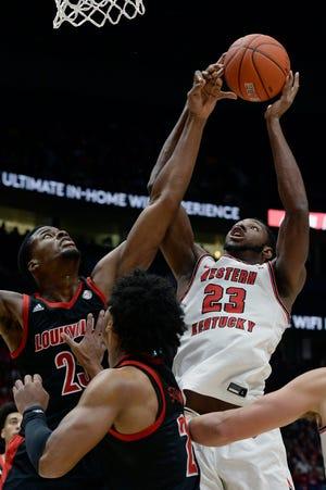 Western Kentucky center Charles Bassey (23) shoots against Louisville center Steven Enoch, top left, during the first half of an NCAA college basketball game Friday, Nov. 29, 2019, in Nashville, Tenn. (AP Photo/Mark Zaleski)