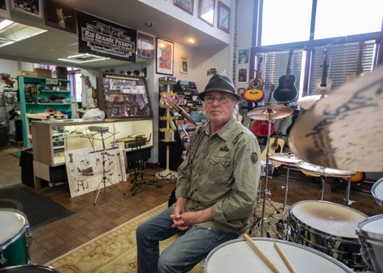 Evan Leake, who has managed Consignment Music for 10 years, sits in front of a drum set in Memphis, Tenn., on Friday, Nov. 29, 2019.