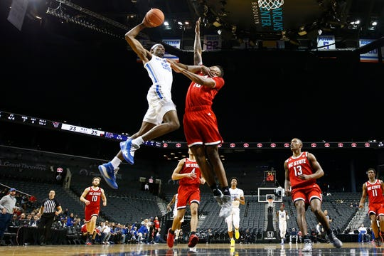 Memphis Tigers forward Precious Achiuwa is fouled while trying to dunk over NC State Wolfpack forward	Manny Bates during their game at the Barclays Center in Brooklyn, NY on Thursday, Nov. 28, 2019.