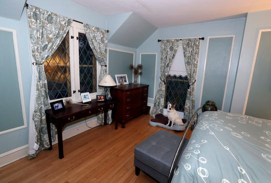 The master bedroom is painted in two calming blue tones with a blend of formal and contemporary patterns. Lola rests on her dog bed under a lattice leaded glass window.