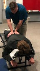 Oconomowoc chiropractor Matt Waro, in blue, is the team chiropractor for the Marquette University hockey team.
