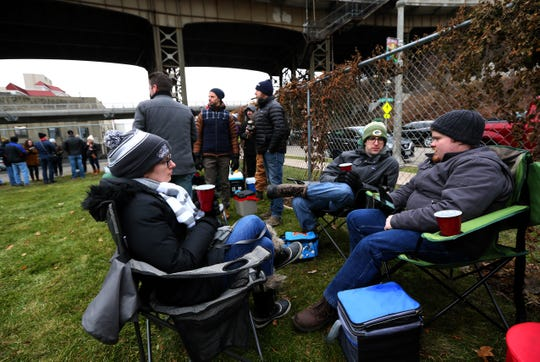 Maggie Brooks, from left, her husband Sean and Alex Gratton wait with others in an overflow area while waiting for Lakefront Brewery to open for its Black Friday beer.