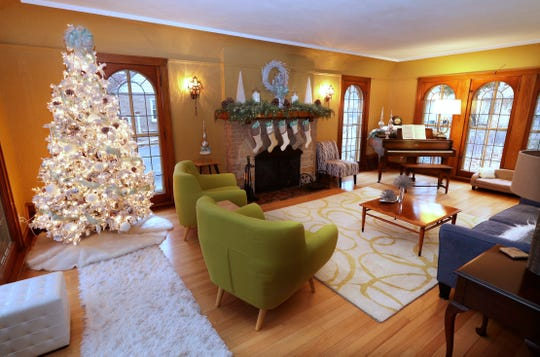 An icy winter theme in the living room includes a live flocked tree, greenery on the mantel and aqua accents.