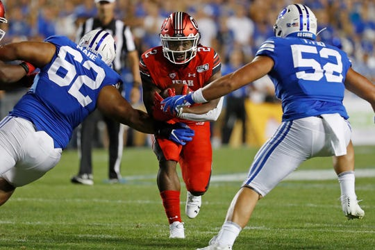 Utah running back Zack Moss (2) runs the ball against BYU defensive linemen Atunaisa Mahe (62) and Trajan Pili (52) in the first quarter at LaVell Edwards Stadium on Aug. 29, 2019, in Provo, Utah.