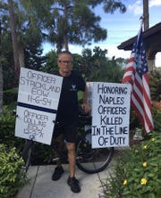 Bob Votruba is pictured with his bike and signs honoring fallen Naples Police Department officers.