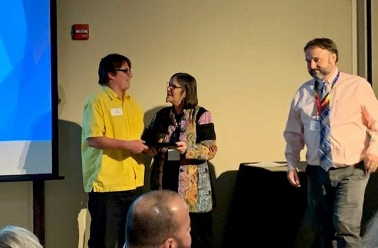 Cody Vanvalkenburg of YES Club receives one of the Outstanding Youth Volunteer awards from Licking County Mental Health America executive director Penny Sitler, as YES Club director Ethan Pound looks on.