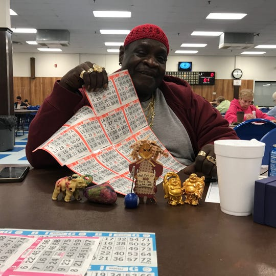 Retired bus driver Garry Johnson with his taped together cards. In front of him are his good luck charms, which include two laughing Buddhas, an elephant and the rock his son painted for him. In numerous cultures elephants with trunks curled upwards are symbols of good luck.