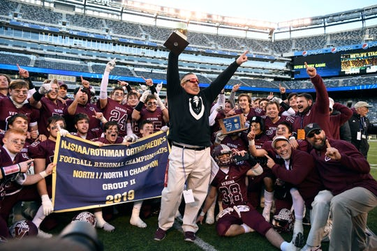 Verona head coach Kevin Batty holds the North Group 2 championship trophy after defeating Lyndhurst, 41-0, at MetLife Stadium on Friday, Nov. 29, 2019, in East Rutherford.