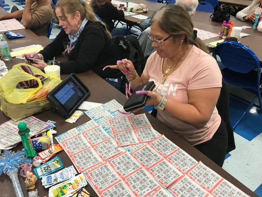 King Cardino, a retired postal worker, assembles her bingo cards. Players often tape together their various cards for a given game to help keep track of the action. Cardino also has a computer that is loaded with cards and keeps track of those cards. In front of her are numerous keepers, or side games.