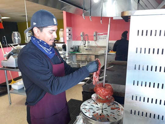Daniel Mata loads pastor meat on the trompo at Taqueria Las Catrinas before opening on Tuesday, Nov. 26, 2019.