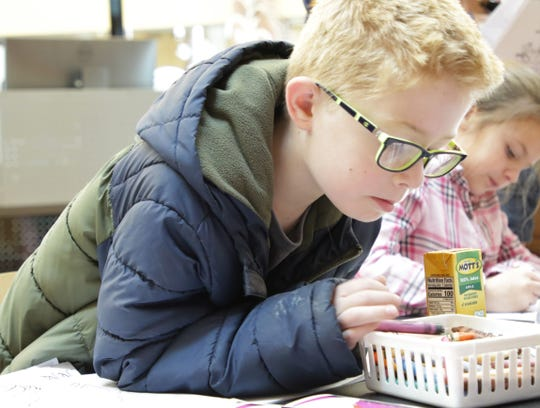 James Vest looks for a crayon to use during a coloring party on Nov. 27 at the Farmington Public Library.