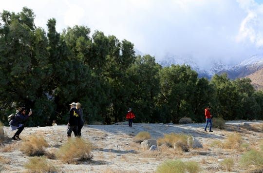 People take photos of the snow on the mountains from this view from N. Indian Canyon Drive in Palm Springs, Calif., on Friday, November 29, 2019.