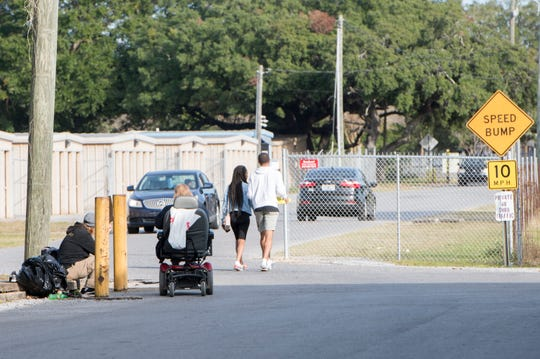 A steady stream of cars, pedestrians and motorized wheelchairs make their way along Cameron Lane in Pensacola on Friday.