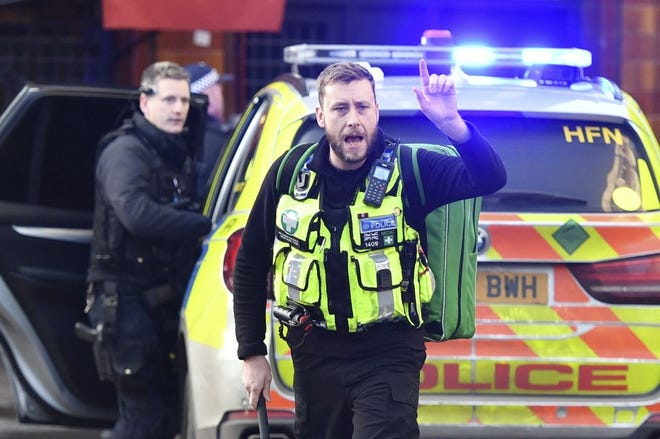 """Police and emergency services at the scene of an incident on London Bridge in central London following a police incident, Friday, Nov. 29, 2019. British police said Friday they were dealing with an incident on London Bridge, and witnesses have reported hearing gunshots. The Metropolitan Police force tweeted that officers were """"in the early stages of dealing with an incident at London Bridge."""" (Dominic Lipinski/PA via AP)"""