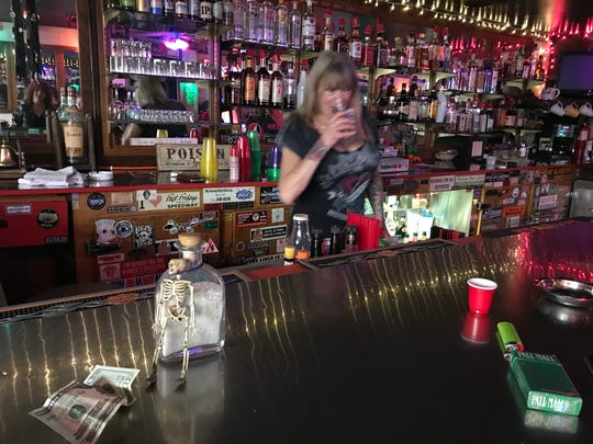 "Kathy Eastland, owner of the Wonder Bar, takes out the ashes of ""Rotten Ron"" from behind the bar on Thanksgiving Day 2019."