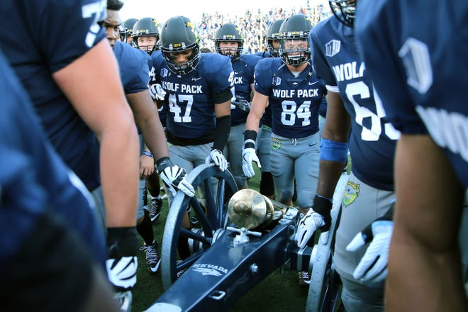 Nevada players surround the Fremont Cannon after the Wolf Pack's win over UNLV in the 2017 game in Reno.