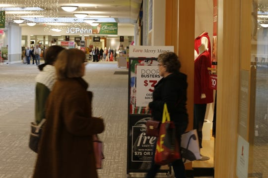 Shoppers pass a sign announcing Black Friday specials Friday in Richmond Mall.
