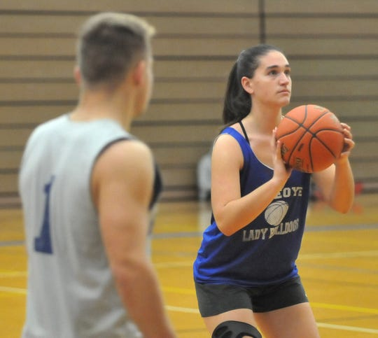 Gabby Trippi lines up a shot during a recent practice at Honeoye, where she and classmate April Washburn are members of the boys basketball team after Honeoye announced it will not field a girls varsity team this season.