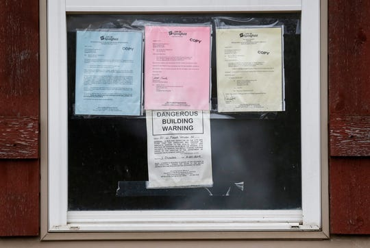 A dangerous building warning and other notices from the city of Springfield are attached to the window of a home at 801 W. Mount Vernon St., on Friday, Nov. 29, 2019.