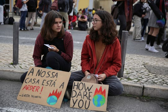 "Two young demonstrators sit on the ground with posters quoting Swedish climate activist Greta Thunberg, in Lisbon during a worldwide protest demanding action on climate change, Friday, Nov. 29, 2019. Thunberg is expected to arrive in Lisbon in the next days before geading to the COP 25 climate conference in Madrid. Poster at left reads in Portuguese, ""Our house is on fire"". (AP Photo/Armando Franca)"