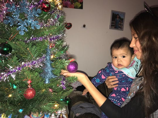 Maite Perez, 11, shows her baby sister Odalis, 6 months, their festive ornaments. The young children will receive new coats through Operation Noel.